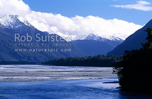 The mighty Arawhata River with the snow cloaked Haast range beyond, South Westland, Westland District, New Zealand (NZ) stock photo.