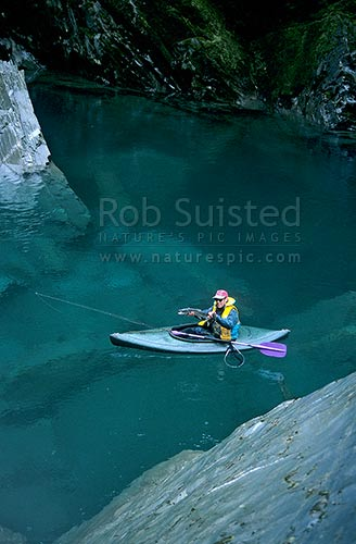 Fisherman with trout caught from kayak - 'Tomtit Grotto' gorge. (model released), South Westland, Westland District, New Zealand (NZ) stock photo.