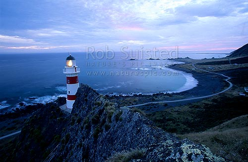 Cape Palliser Lighthouse and coast at dusk, Cape Palliser, South Wairarapa District, Wellington Region, New Zealand (NZ) stock photo.