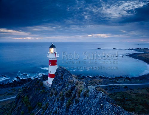 Cape Palliser Lighthouse and Palliser Bay at dusk, Cape Palliser, South Wairarapa District, Wellington Region, New Zealand (NZ) stock photo.
