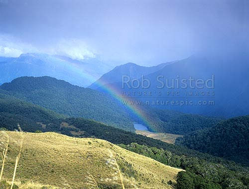 Lakes Bux and Porm nestled in the Thomson Range, above the Arawhata River. Rainbow over lake, South Westland, Westland District, West Coast Region, New Zealand (NZ) stock photo.